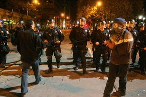 OAKLAND, CA -  NOVEMBER 14:  Police move protestors back during the eviction of the Occupy Oakland camp on November 14, 2011, in Oakland, California. In the wake of violent confrontations with police, vandalism and the recent shooting near the encampment, Oakland mayor Jean Quan and city administrators issued eviction notices to protesters at the Occupy Oakland encampment.  (Photo by Mathew Sumner/Getty Images)