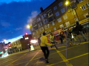 LONDON, ENGLAND - AUGUST 08:  In this video screen grab a cyclist rides past youths in the street in Peckham on August 8, 2011 in London, England. Pockets of rioting and looting continues to take place in various boroughs of London this evening, as well as in Birmingham, prompted by the initial rioting in Tottenham and then in Brixton on Sunday night. It has been announced that the Prime Minister David Cameron and his family are due to return home from their summer holiday in Tuscany, Italy to respond to the rioting. Disturbances broke out late on Saturday night in Tottenham and the surrounding area after the killing of Mark Duggan, 29 and a father-of-four, by armed police in an attempted arrest on August 4.  (Photo by Dan Kitwood/Getty Images)