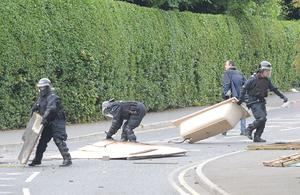 Police in riot gear clear a makeshift barricade on the Antrim Road in Lurgan last night as rioting continued throughout the day in the republican Kilwilkee area