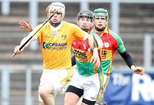Antrim's Neil McManus tries to get away from Carlow's Des Shaw and Colin Hughes at Casement Park yesterday
