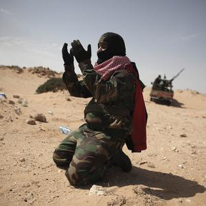 A Libyan pro-democracy activist prays on the outskirts of the eastern town of Ras Lanouf, Libya (AP)