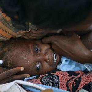 A child suffering cholera symptoms is comforted at the hospital in Grande-Saline, Haiti (AP)