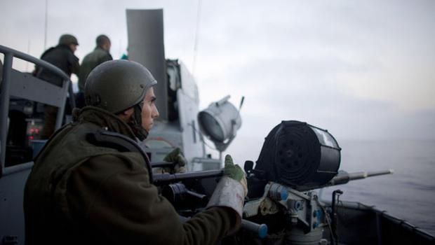 Israeli Navy soldier stands behind a machine gun aboard a missile ship while Israeli Navy soldiers intercept several boats headed towards the Gaza Strip