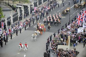 Prince William and his new wife Kate travel in the 1902 State Landau carriage along the Processional Route to Buckingham Palace, in London. PRESS ASSOCIATION Photo. Picture date: Friday April 29, 2011. See PA story WEDDING Lead. Photo credit should read: Damien Meyer/PA Wire
