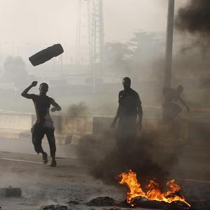 Angry youths burn debris following the removal of a fuel subsidy by the Nigerian government (AP)