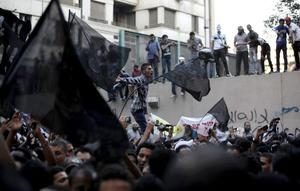 Egyptian protesters climb the walls of the U.S. embassy while others chant anti U.S. slogans during a protest in Cairo, Egypt