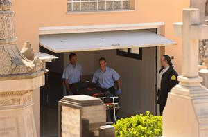 The body of Stephen Gately is wheeled out of a morgue in Palma de Mallorca