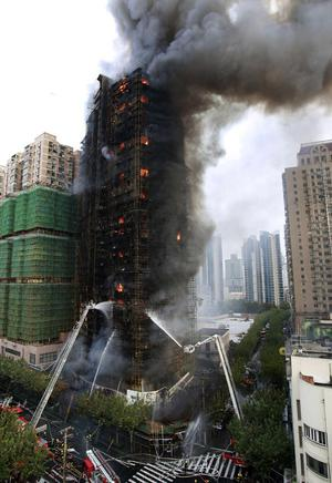 Firefighters spray water on an apartment building on fire in the downtown area of Shanghai, east China, on Monday Nov. 15, 2010. The state news agency says the fire in the high-rise apartment building in China's business center of Shanghai has killed at least eight people and injured more than 90. (AP Photo) CHINA OUT