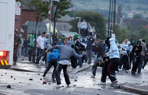Youths clash with police following an Orange Order march past Ardoyne shops in north Belfast