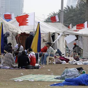 Bahraini anti-government protesters sleep outside their tents as others have breakfast at the Pearl roundabout in Manama, Bahrain