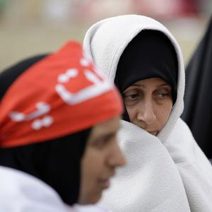 Bahraini anti-government protesters wrap themselves up in blankets against morning cold at the Pearl roundabout in Manama