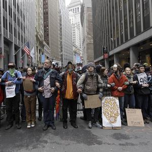 The New York Stock Exchange is seen in the background as demonstrators affiliated with the Occupy Wall Street movement lock arms (AP)