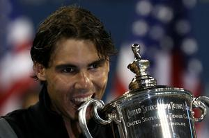 Rafael Nadal of Spain bites the championship trophy during the trophy ceremony after defeating Novak Djokovic of Serbia