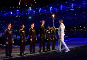 Sir Steve Redgrave hands the torch to young torch bearers Callum Airlie, Jordan Duckitt, Desiree Henry,  Katie Kirk, Cameron MacRitchie, Aidan Reynolds and Adelle Tracey during the London Olympic Games 2012 Opening Ceremony at the Olympic Stadium, London. PRESS ASSOCIATION Photo. Picture date: Friday July 27, 2012. See PA story OLYMPICS Ceremony. Photo credit should read: Owen Humphreys/PA Wire. EDITORIAL USE ONLY