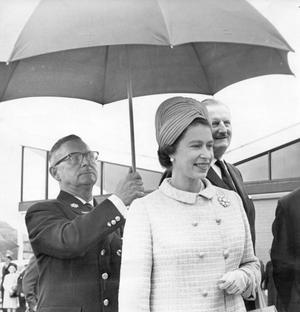 The Queen, Elizabeth 11. 1966 visit.The Queen shelters from the rain as she opens the new Queen's University playing fields at Upper Malone. On the right is Tyrone Guthrie, Chancellor of the University. Holding the umbrella is Ranger James Chasty.  5/7/1966