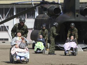 ALTERNATE CROP OF TOK890 OF MARCH 13, 2011 - Futaba Kosei Hospital patients are assisted by Japan Self Defense Force personnel as they disembark from a helicopter in the compound of Fukushima Gender Equality Centre in Nihonmatsu, Fukushima Prefecture, northeastern Japan, Sunday morning, March 13, 2011 after being evacuated from the hospital in Futaba town near the troubled Fukushima Dai-ichi nuclear complex. They might have been exposed to radiation while waiting for evacuation when an explosion of Unit 1 reactor of the complex blew off the top part of its walls on Saturday, one day after a strong earthquake and tsunami hit northeastern Japan. (AP Photo/The Yomiuri Shimbun, Daisuke Tomita)  JAPAN OUT, CREDIT MANDATORY