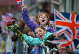 ENNISKILLEN, NORTHERN IRELAND - JUNE 26:  Children wave Union Jack flags and hold out floral bouquets as Queen Elizabeth II and Prince Philip, Duke of Edinburgh arrive to visit Macartin's Cathedral on June 26, 2012 in Enniskillen, Northern Ireland. The Queen and Duke of Edinburgh, on a Diamond Jubilee visit to Northern Ireland, are due to meet with former IRA leader and NI's Deputy First Minister Martin McGuinness.  (Photo by Jeff J Mitchell/Getty Images)