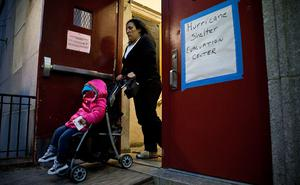 NEW YORK, NY - OCTOBER 28:  A woman and child leave Seward Park High School, which is doubling as an evacuation center for Hurricane Sandy, on October 28, 2012 in New York City. Sandy, which has already claimed over 50 lives in the Caribbean, is predicted to bring heavy winds and floodwaters as the mid-atlantic region prepares for the damage.  (Photo by Andrew Burton/Getty Images)