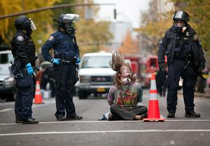 PORTLAND - NOVEMBER 13: A young protesters hair swishes through the air as he nods his head after he was placed in handcuffs and arrested near the Occupy Portland encampment November 13, 2011 in Portland, Oregon. Portland police have reclaimed the two parks in which occupiers have been camping after a night of brinksmanship with protesting crowds of several thousands. (Photo by Natalie Behring/Getty Images)