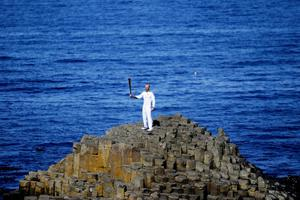 The Olympic torch is carried onto the famous landmark of the Giant's Causeway outside the village of Bushmills, Co.Antrim by carrier Peter Jack