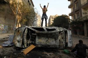A protester stands on top of a burned car during clashes with Egyptian riot police, unseen, in Tahrir Square in Cairo, Egypt, Monday, Nov. 21, 2011. Security forces fired tear gas and clashed Monday with several thousand protesters in Cairo's Tahrir Square in the third straight day of violence that has killed at least two dozen people and has turned into the most sustained challenge yet to the rule of Egypt's military.(AP Photo/Khalil Hamra)