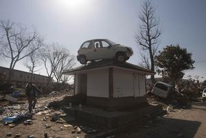 A car sits on top of a small building in a destroyed neighborhood in Sendai, Japan, on Sunday, March 13, 2011 after it was washed into the area by the tsunami that hit northeastern Japan. AP Photo/David Guttenfelder)