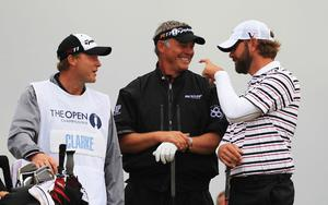 Darren Clarke of Northern Ireland waits with caddy John Mulrooney and  Lucas Glover (R) of the United States during the third round of The 140th Open Championship at Royal St George's on July 16, 2011 in Sandwich, England