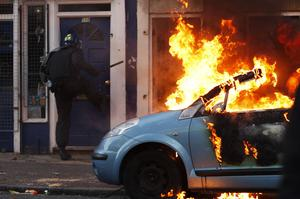 LONDON, ENGLAND - AUGUST 08:  A riot police officer attempts to break down the door of a house next to a burning car as he is targeted by rioters after local residents claimed a baby was still in the property in Clarence Road in Hackney on August 8, 2011 in London, England. Pockets of rioting and looting continues to take place in various boroughs of London this evening, as well as in Birmingham, prompted by the initial rioting in Tottenham and then in Brixton on Sunday night. It has been announced that the Prime Minister David Cameron and his family are due to return home from their summer holiday in Tuscany, Italy to respond to the rioting. Disturbances broke out late on Saturday night in Tottenham and the surrounding area after the killing of Mark Duggan, 29 and a father-of-four, by armed police in an attempted arrest on August 4.  (Photo by Dan Istitene/Getty Images)