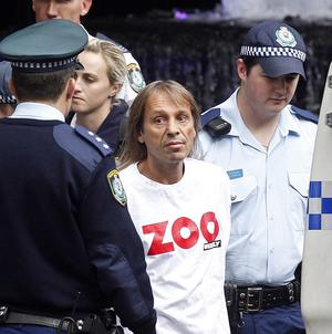 French stuntman Alain Robert is led into a waiting police van after his arrest in Sydney