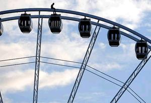 A man climbs to the top of Belfast's Big Wheel