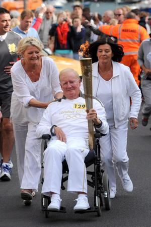 Brendan Duddy carrying the Olympic flame during the Torch Relay leg between Dervock and Portrush