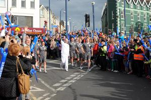 Stewart Duguid carrying the Olympic flame during the Torch Relay leg between Dervock and Portrush