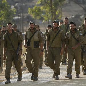 Israeli soldiers march in a gathering area near the Israel Gaza Strip border, in southern Israel (AP)