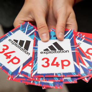A member of the War on Want campaign group holds fake price labels for Adidas clothing outside the Adidas store on Oxford Street, central London