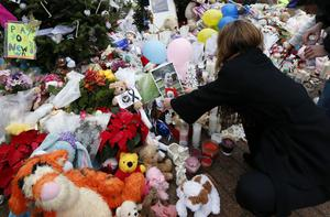 A woman puts a photo of a child on a makeshift memorial in the Sandy Hook village of Newtown, Conn., as the town mourns victims killed in a school shooting, Monday, Dec. 17, 2012. (AP Photo/Julio Cortez)