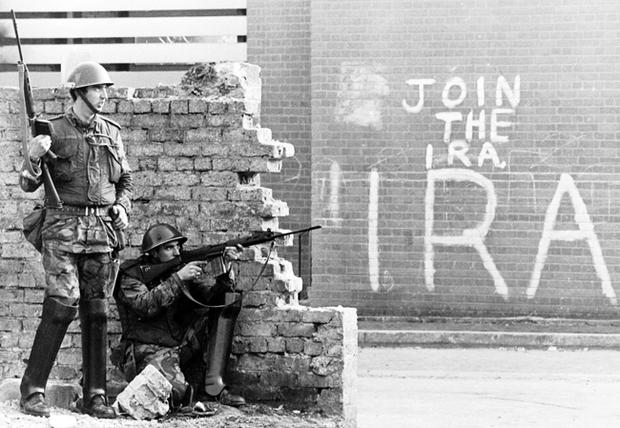 Armed soldiers behind a wall on Londonderry's Bogside.