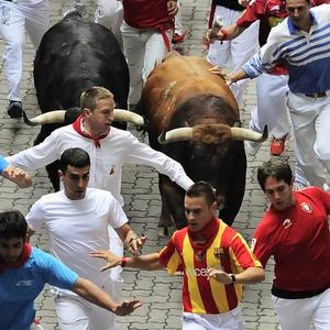 Revelers run on the Callejon Way during the third running of the bulls at the San Fermin fiestas, in Pamplona, northern Spain (AP)