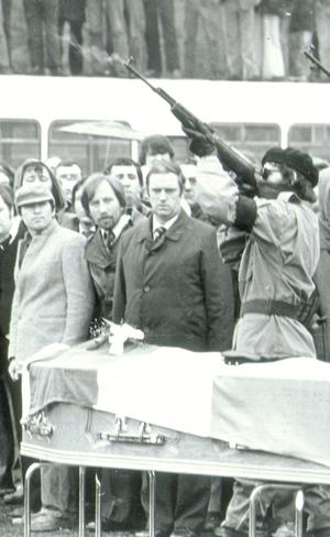 Hunger striker Bobby Sands coffin, at Milltown Cemetery. Masked gunmen fire a volley of shots.