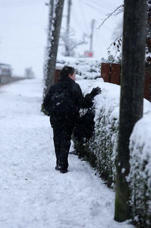 A school boy makes his way home after giving up on trying to get to school