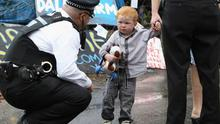 A police officer speaks to a child resident of the Dale Farm travellers' settlement at the camp's entrance. September  2011 in Basildon, England.
