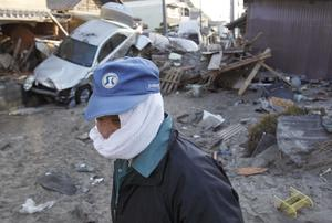 A man, with his face covered to protect against dust, looks out at the damage Monday, March 14, 2011, in Yotsukura, Japan, three days after a giant quake and tsunami struck the country's northeastern coast. (AP Photo/Gregory Bull)