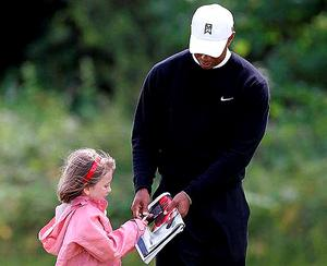 Tiger Woods signs an autograph for six-year-old Ava Mulhall