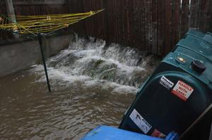 Water pours into the  garden of a house in Bealaghmor in the Ballymagroarty area of Derry