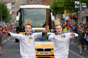 John (L) and Edward Grimes, aka Jedward, carry the Olympic Flame on day 19 of the London 2012 Olympic Torch Relay on June 6, 2012  in Dublin, Ireland