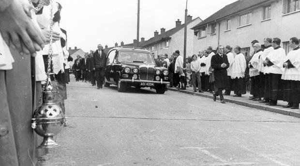 Father Hugh Mullan. Shot at Moyard Park. 9/8/1971 THE FUNERAL HEARSE CARRYING THE BODY OF FATHER HUGH MULLAN TRAVELS ALONG THE ROAD IN BALLYMURPHY ESTATE. 12/8/1971
