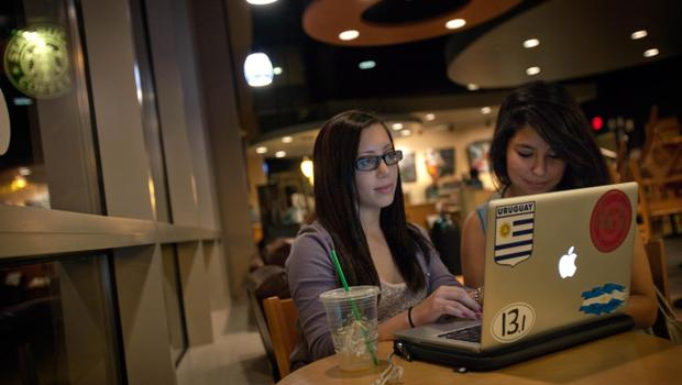 Georgia Tech students Sarah Malis, 20, left, and Marcela Moreno, 20, sit around an Apple laptop computer at a Starbucks  store Wednesday, Oct. 5, 2011 in Atlanta. Steve Jobs, the Apple founder and former CEO who invented and masterfully marketed ever-sleeker gadgets that transformed everyday technology, from the personal computer to the iPod and iPhone, died Wednesday. (AP Photo/David Goldman)