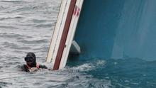 A rescue diver swims next to the Costa Concordia cruise liner, two days after it ran aground off the tiny Tuscan island of Giglio, Italy, Monday, Jan. 16, 2012. The captain of a cruise liner that ran aground and capsized off the Tuscan coast faced accusations from authorities and passengers that he abandoned ship before everyone was safely evacuated as rescuers found another body on the overturned vessel. (AP Photo/Gregorio Borgia)