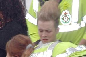 Edward Grimes of 'Jedward' seen being taken away to a waiting ambulance, with his left leg secured in a brace, after falling off stage during a performance of Ghostbusters at T4 on the beach. He was accompanied by his brother Johan Grimes and Liam McKenna, Weston-super-Mare, UK - 04.07.10. Pictures: VIPIRELAND.COM *** Local Caption ***