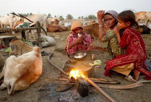 A Pakistani mother and her daughters make some tea over a fire, living on the street after the floods forced them to flee
