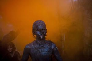 Covered by mud, a man parades at a mud party during Carnival celebrations in Paraty,  Brazil, Saturday, March 5,  2011. The five-day annual carnival celebration officially started Friday and is expected to draw about 756,000 visitors, both foreign and Brazilian, who will pack hotels to nearly 100 percent capacity and spend about $559 million, according to Rio state's tourism department. (AP Photo/Rodrigo Abd)